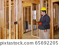 Inspector with yellow hard hat checking electrical 65692205