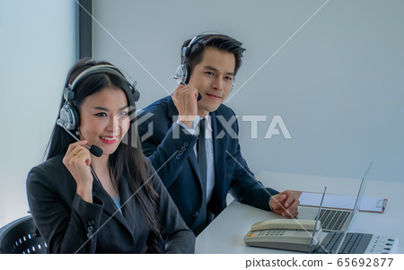 Side view of beautiful young business woman and handsome businessman in headsets using laptops while working in office. Man and woman are looking at camera. 65692877