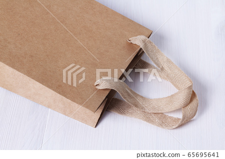 Packaging template mock up. Handle made of natural materials. Part of the package. Disposable small craft paper bag for takeaway on white table in the interior. Flatlay mock up. Place for text 65695641