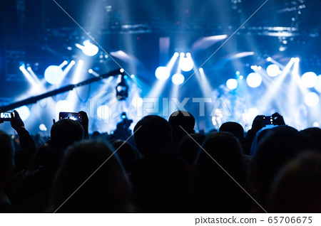 Silhouette of a concert crowd. The audience looks 65706675