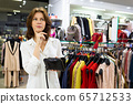 A beautiful caucasian woman choose dresses in a big mall, smiles and thinks 65712533