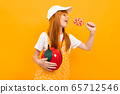 Pretty girl with red hair posing on camera with little apple bag eats a lolipop isolated on yellow 65712546
