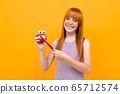 Beautiful caucasian woman with red hair smiles and recommend brushes teeth isolated on yellow 65712574