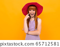 Pretty young girl with red hir and big red hat smiles isolated on white background 65712581