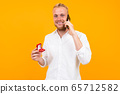 blond european man makes an offer holding a ring in a box talking on the phone on a yellow 65712582