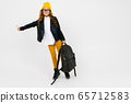 European attractive girl dressed in a yellow hat, glasses and a leather jacket with a backpack in 65712583