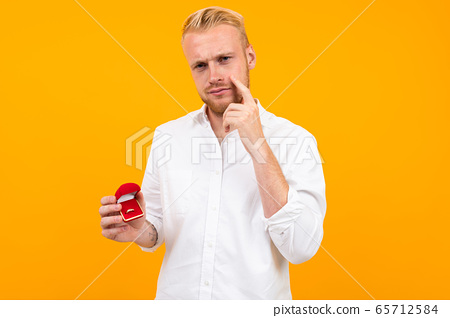blond European man makes a proposal holding a ring in a red box on a yellow background. 65712584