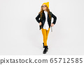 Teenager caucasian girl with yellow hat holds a big backpack in her hands isolated on white 65712585