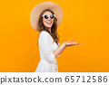 Caucasian woman with hat is posing on camera isolated on yellow background 65712586