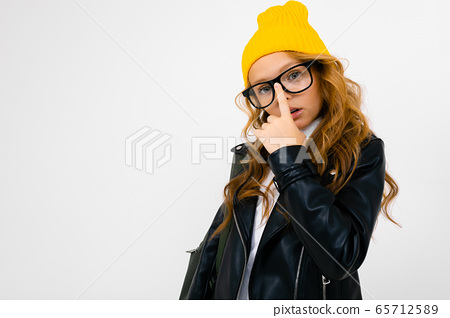 European attractive girl dressed in a yellow hat, glasses and a leather jacket with a backpack on 65712589