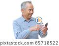 """一個男人按下智能手機上的""""贊""""按鈕 65718522"""