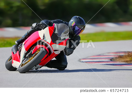 Motorcycle leaning into a fast corner on race 65724715