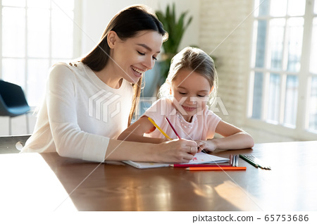 Happy mom and small daughter painting together 65753686