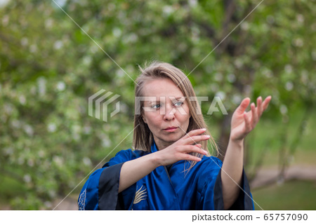 girl practices tai Chi against the background of a blooming Apple tree 65757090