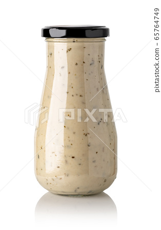 Closed glass jar of white garlic and herb sauce 65764749