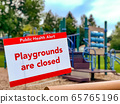 Playground is Closed Sign posted in front of an empty Playground 65765196