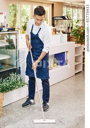 Coffeeshop owner wiping floor 65779933