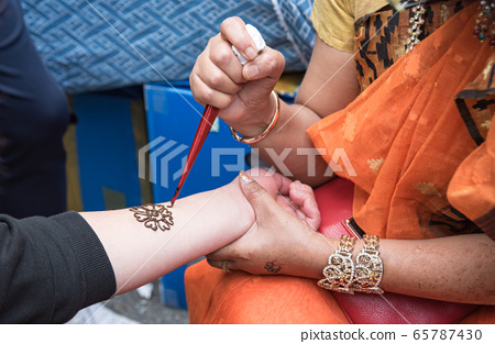 Indian woman drawing henna 65787430