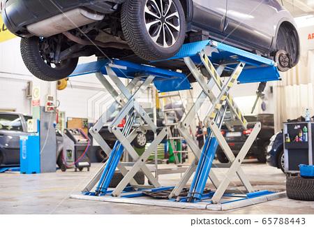 Automobile raised on lift for repairing in auto repair shop. 65788443