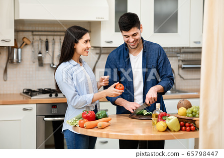 Cheerful couple preparing salad together at home 65798447