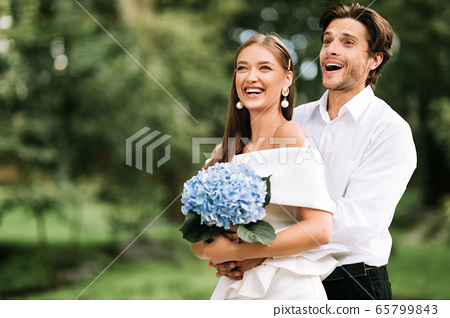 Happy Just-Married Couple Hugging Standing In Park Outside Celebrating Wedding 65799843