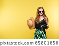 Young girl in straw hat and glasses keeping camera 65801656