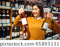 Woman with two bottles of alcohol in grocery store 65803131