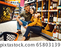 Cheerful couple with cart in grocery supermarket 65803139