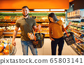 Couple with cart in grocery supermarket together 65803141