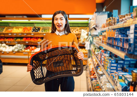 Woman with empty basket in grocery store 65803144