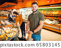 Couple with basket in grocery supermarket together 65803145