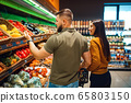 Couple with basket in grocery supermarket together 65803150