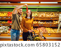 Couple with basket in grocery supermarket together 65803152
