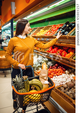 Young woman with basket in grocery store 65803157