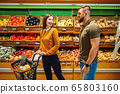 Happy couple with basket in grocery store 65803160