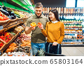Happy couple with basket in grocery store 65803164