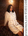 Woman sitting on a hot stone in hamam, sauna 65803168