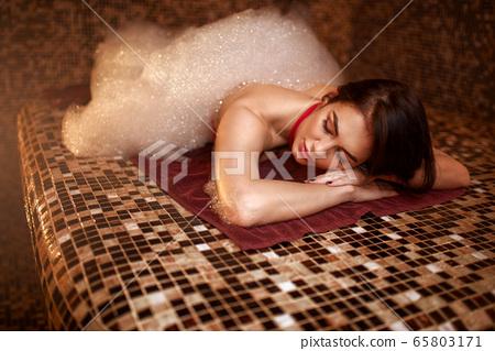 Woman in foam lying on a hot stone in hamam, sauna 65803171