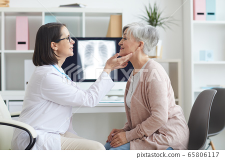 Female Doctor Palpating Neck of Senior Woman 65806117