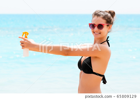 Young woman with sun protection spray for body at 65809129
