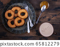 Donuts and coffee cup on wooden table 65812279