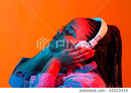Lifestyle concept - Portrait of beautiful African American woman joyful listening to music. 65813419