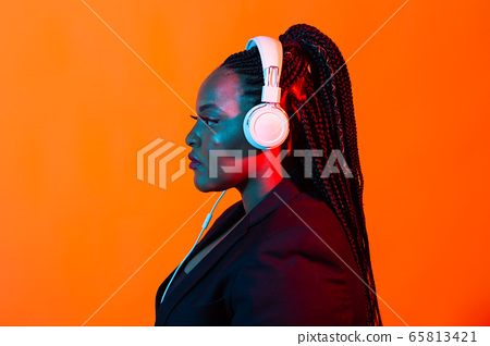 African american young woman listening to music online dancing and singing with headphones, neon light. Music and technology concept. 65813421