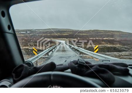 Driving in Iceland, wet road, single-lane bridge 65823079