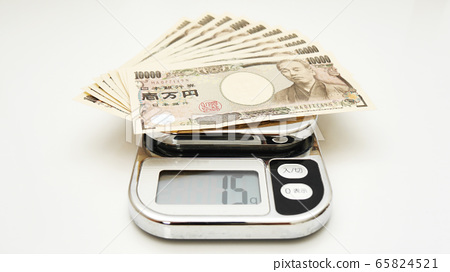 Weigh a bundle of 10,000-yen bills on a scale 65824521