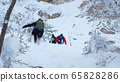 A group of tourists rises to the top of a snow-covered mountain. 65828286