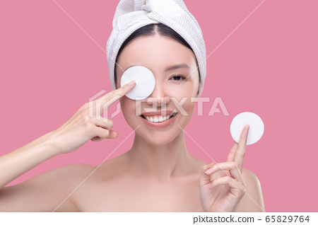 Smiling asian girl in a white headscarf holding sponges for cleaning and closing one eye 65829764