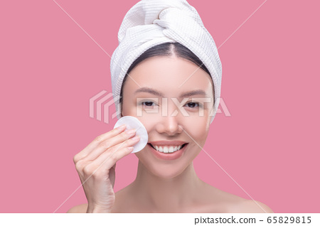 Pretty asian girl in a white headscarf cleaning her face with a sponge and feeling happy 65829815