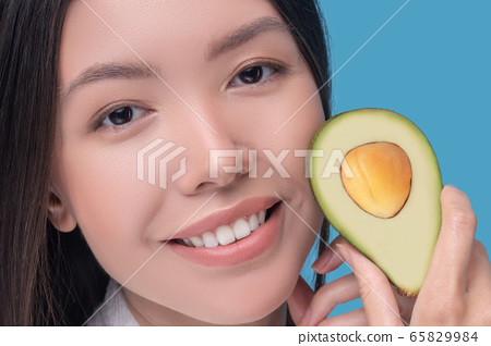 Smiling young asian woman holding a half of avocado 65829984