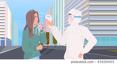 specialist in hazmat suit checking body temperature of woman for coronavirus symptoms covid-19 65830403